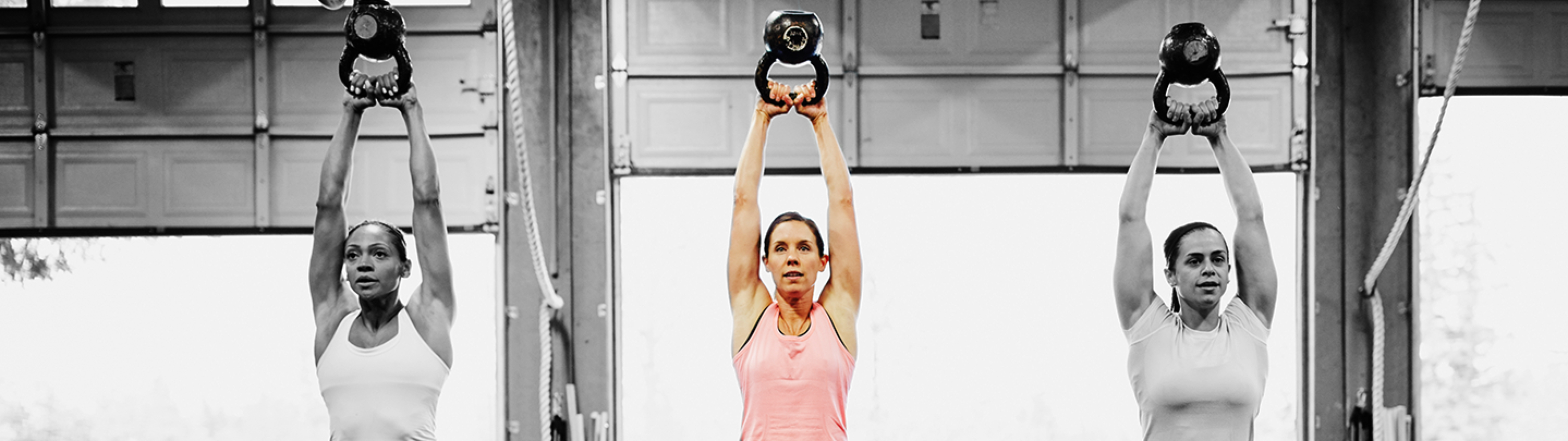 Three women working out with kettle bells